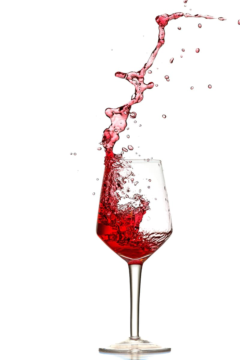 Pouring of red wine in clear long stem wine glass