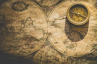 Photography of world map and compass