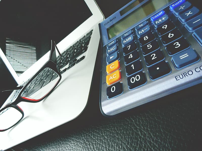 Black and gray calculator on white paper