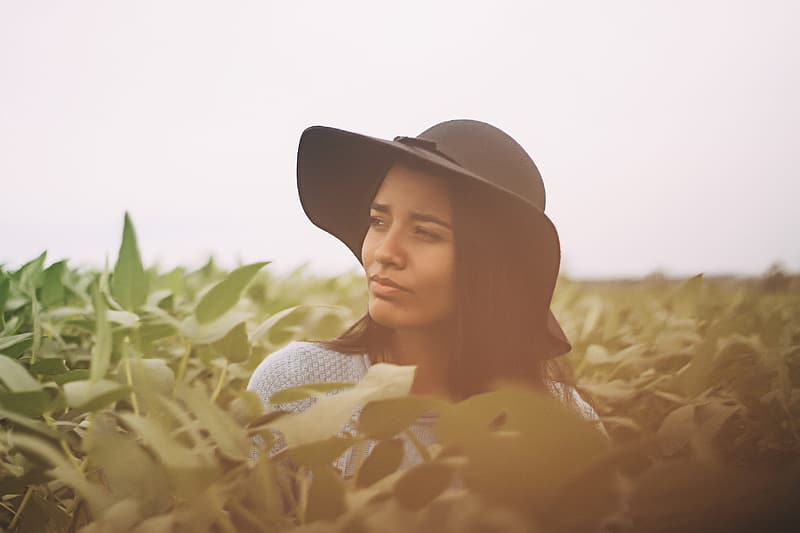 Woman with black hat and white top between green plant under white sky during daytime