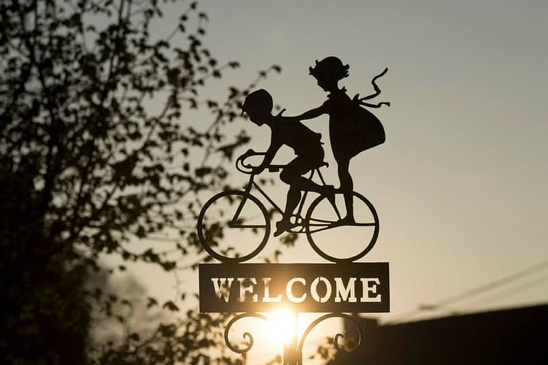 Silhouette of two children on bike with welcome sign