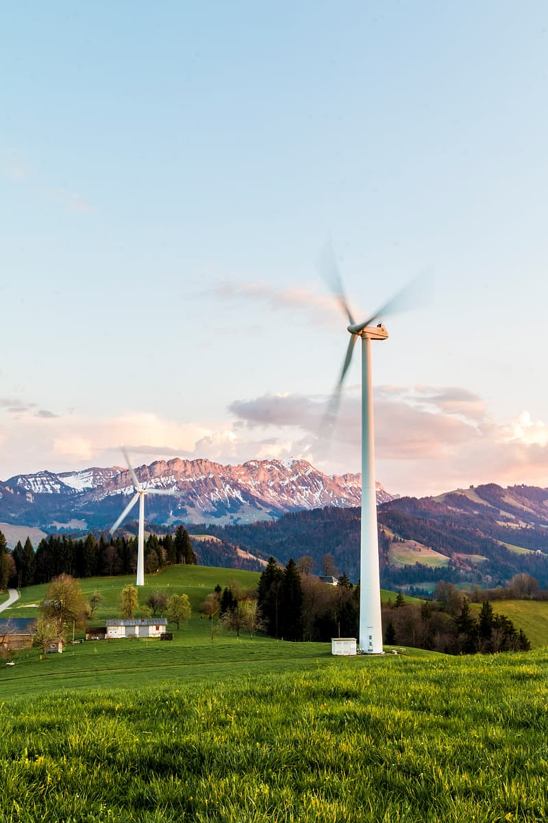 White wind turbines with mountain at distance at daytime