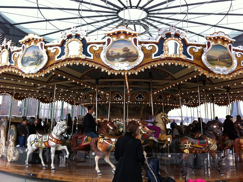 People riding on carousel during daytime
