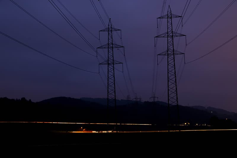 Silhouette of electric towers during sunset