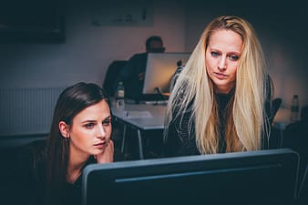 Two women staring in black monitor in dim-lighted room
