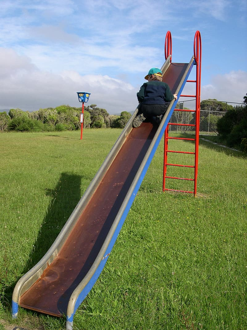 Man in black jacket and black pants climbing on red and brown slide during daytime