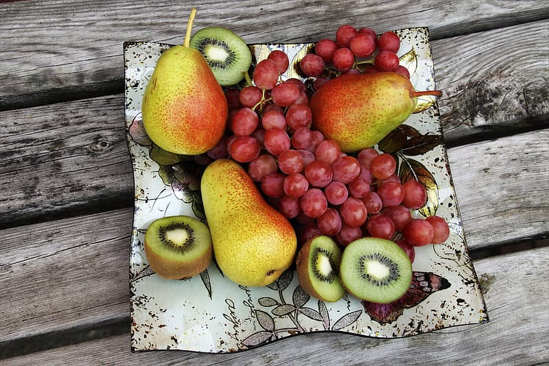 Green apple and red apples on white wooden table