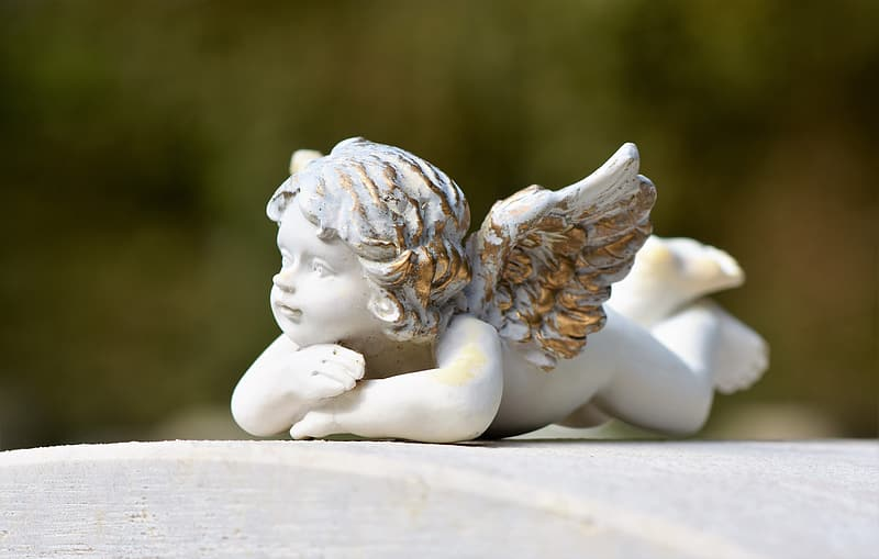 White angel ceramic figurine on brown wooden table