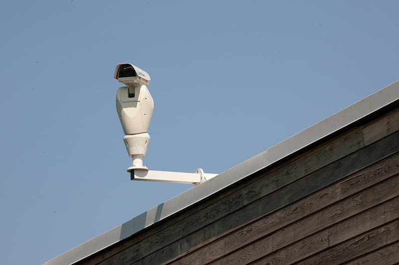 White and black robot on brown wooden roof under blue sky during daytime