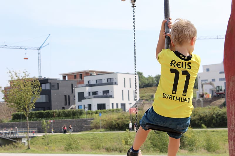 Girl in yellow and black shirt and black shorts on swing during daytime