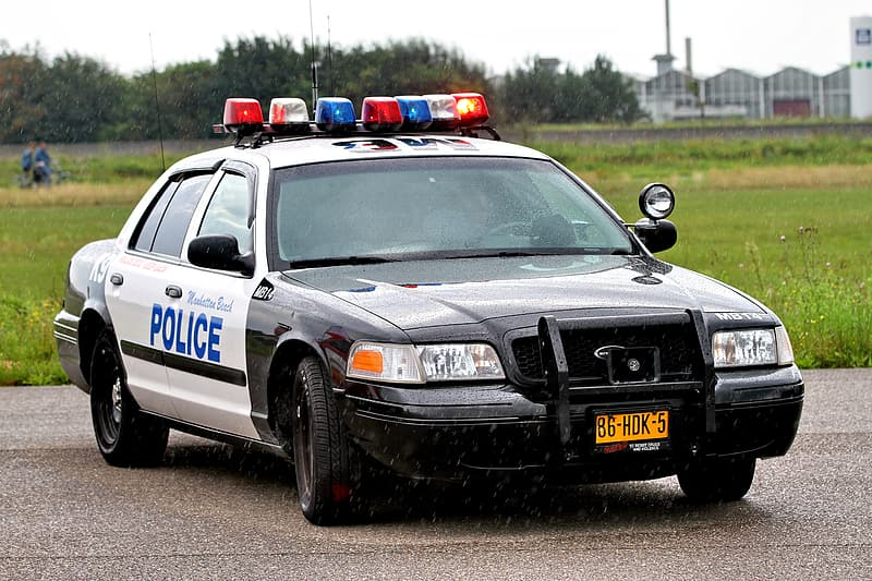 White and blue police car on road during daytime
