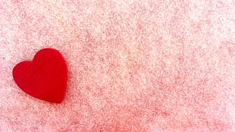 Red heart ornament on top of pink textile