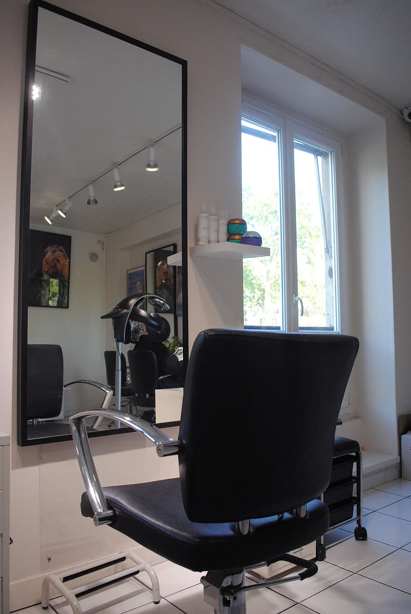 Black leather salon chair in front of mirror
