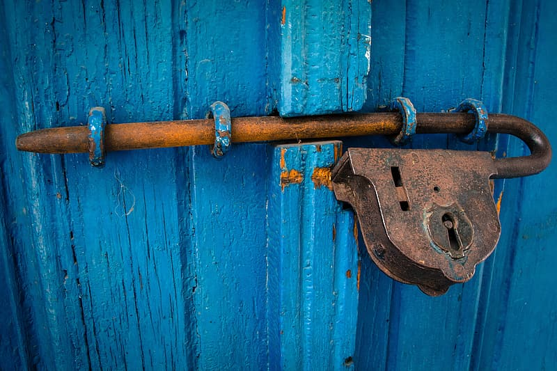 Brown steel padlock on blue wooden door