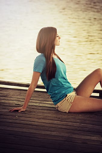 Woman wearing blue v-neck shirt sitting on dock