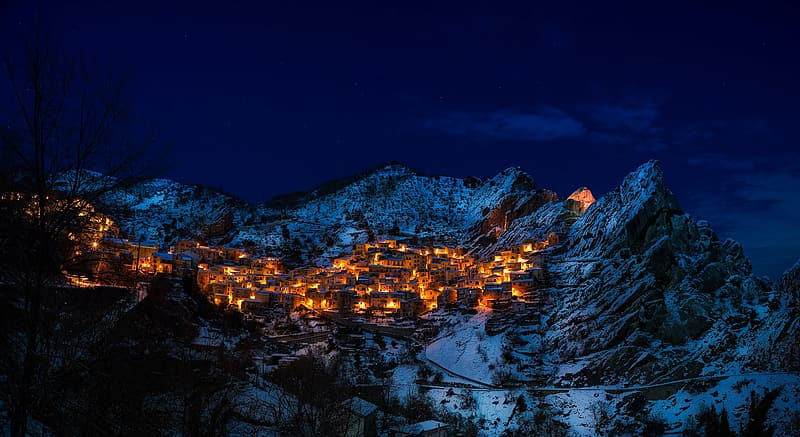 White and brown mountain, areal photo of turned on lights on village on snow filled mountain