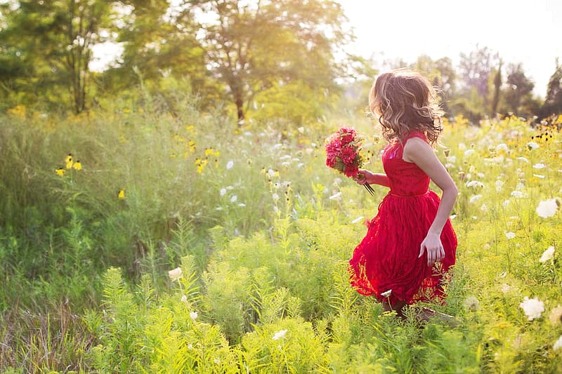 Woman wearing dress while carrying bouquet of flower on a flower field