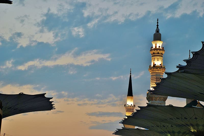 Lighted black and beige tower under blue and white sky
