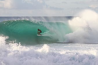 Person surfing with big waves at the beach