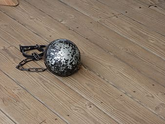Silver ball on brown wooden floor