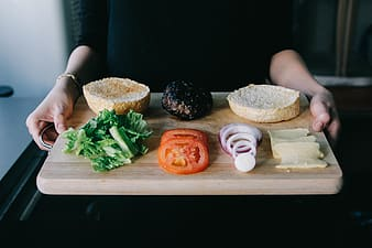 Person holding burger recipe with tray
