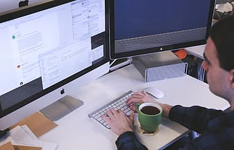 Person in black long-sleeved shirt in front of silver iMac using Apple Magic Keyboard