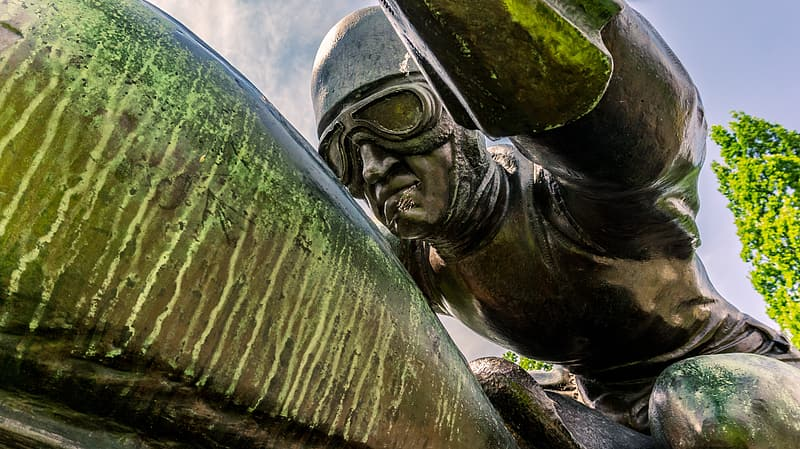 Man wearing half-face helmet and aviator goggles statue