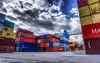 Blue and red cargo containers under cloudy sky during daytime