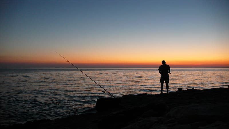 Silhouette of a man near body of water