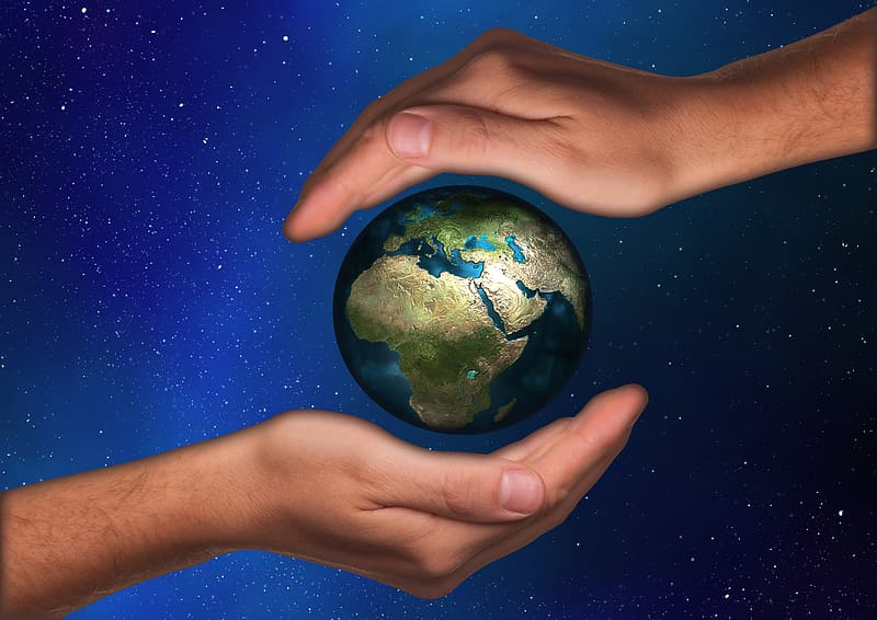 Two human hands and planet earth
