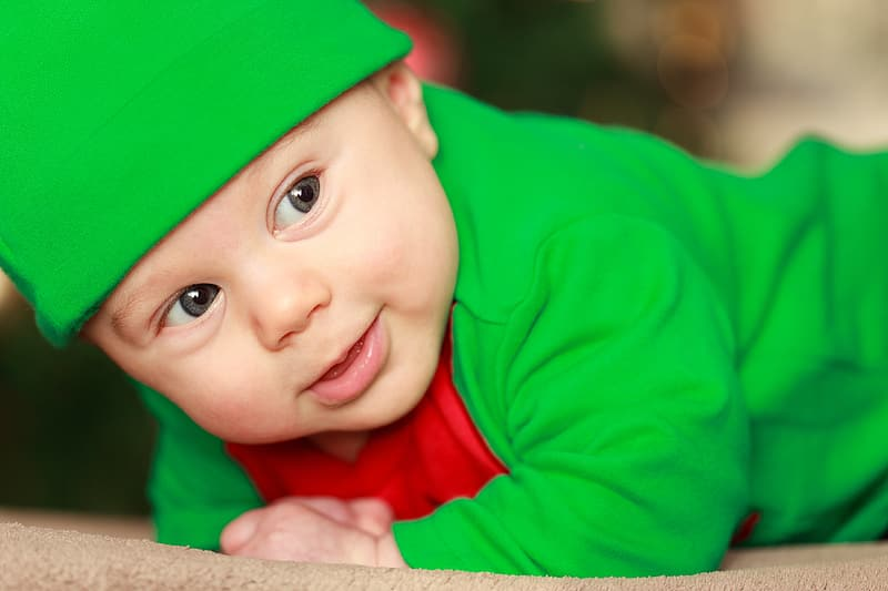 Baby wearing green top and hat