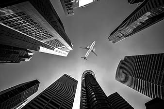 Low angle and grayscale photo of airplane between tall buildings