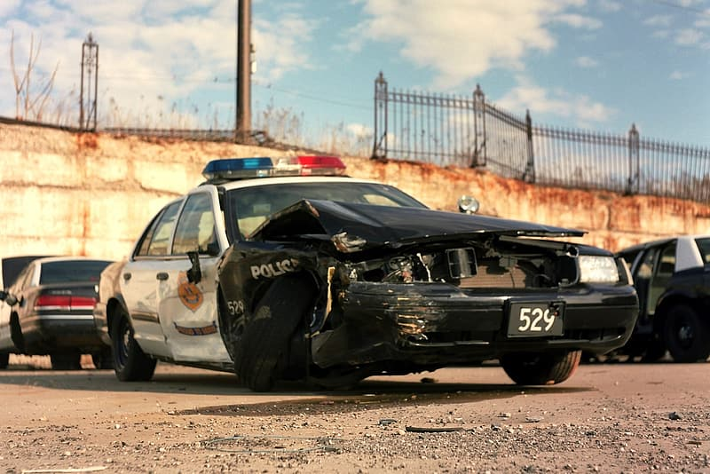 Wrecked black and white police cruiser near other vehicles parked on lot at daytime