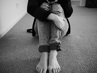Woman sitting on floor in grayscale photography