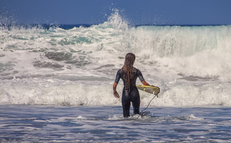 Woman in black wet suit holding yellow surfboard on beach during daytime