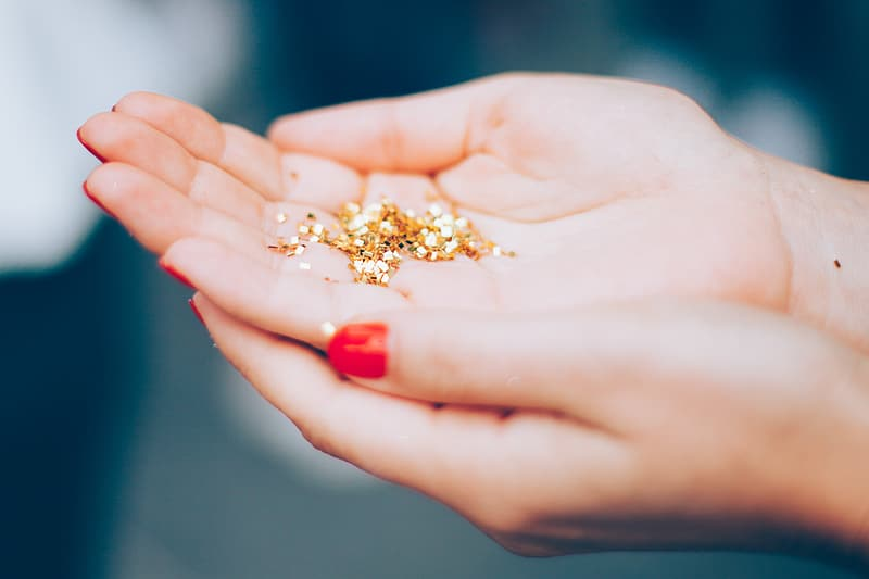 Gold glitters on person's hand