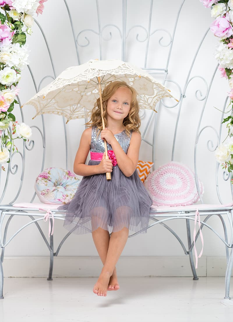 Smiling girl in gray sleeveless dress sitting on white bench holding white umbrella