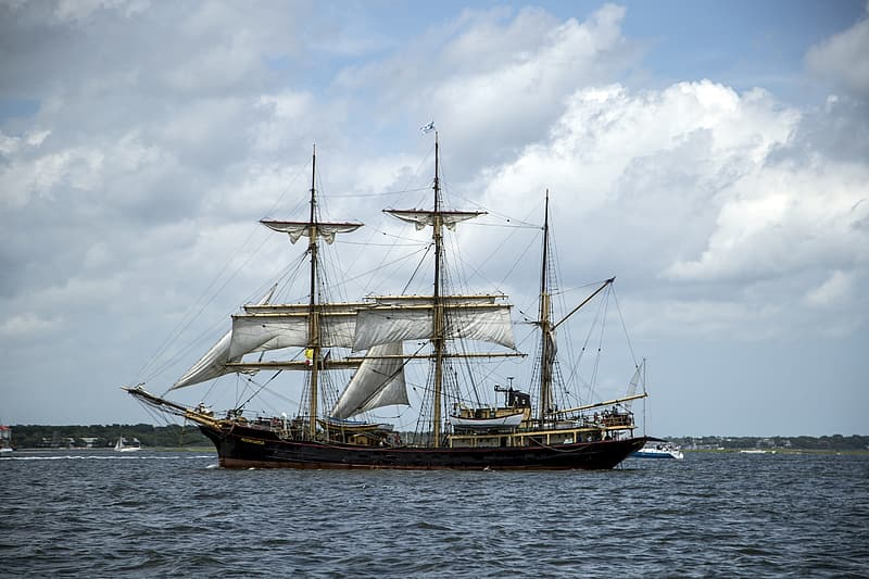 Brown and black ship on sea under white clouds and blue sky during daytime