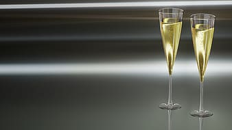 Two clear flute glasses filled with yellow liquid