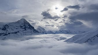 Snow mountain peaks under cloudy sky