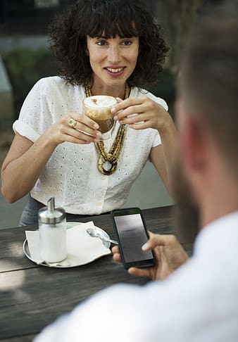 Woman holding clear glass cup in front of man holding smartphone