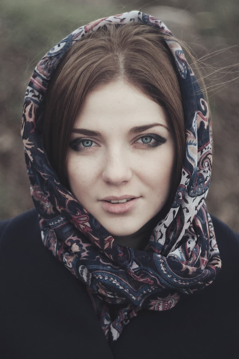 Woman wearing blue, beige, and pink floral head scarf and black jacket