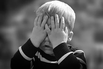 Grayscale photo of boy covering his face weawring black and white striped sweatshirt