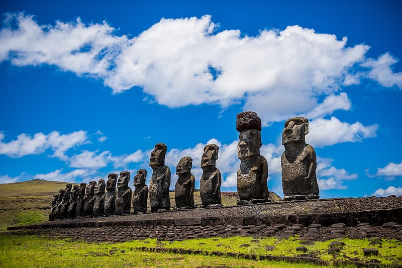 Moai statues under blue and white cloudy skies at daytime