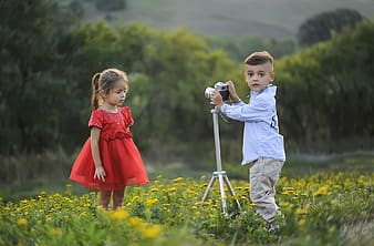 Girl in white and red dress holding camera on yellow flower field during daytime