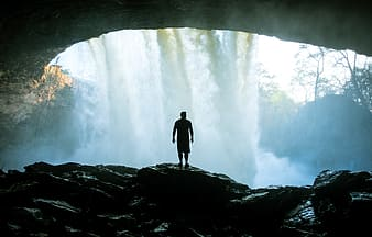 Silhouette of man standing in cave fronting water falls
