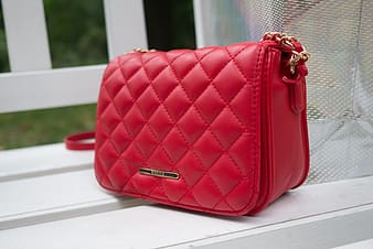 Quilted red leather flap bag on wooden chair