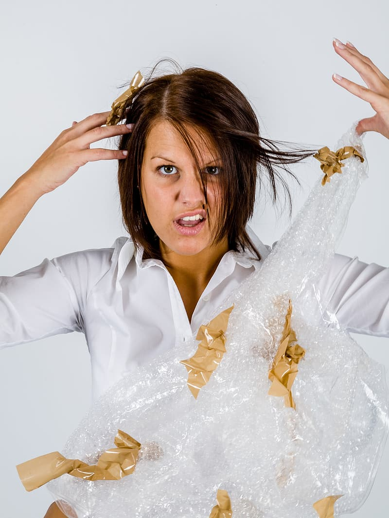 Woman in white top holding bubble wrap