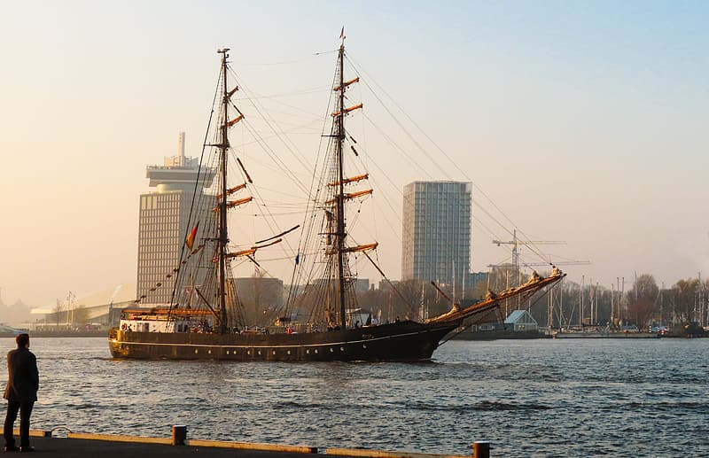 Brown and black ship on sea near city buildings during daytime