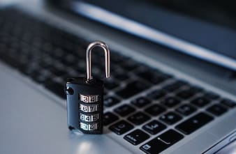 Unlock black and grey numerical combination padlock placed on grey laptop